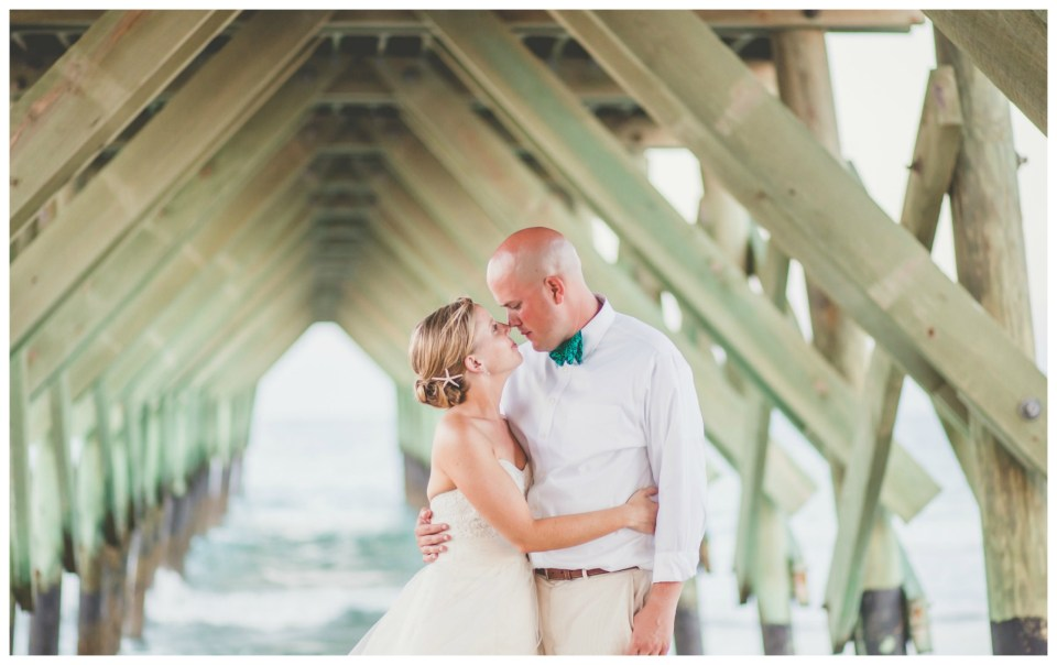 bride and groom kissing under pier