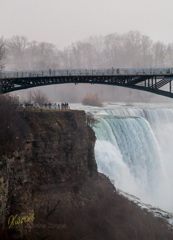 A distant view of the observation deck on the American side of the Niagara Falls, with the tourists that are on top and the water coming down with such force. I took this photo while standing on the Rainbow Bridge between the borders of America and Canada.