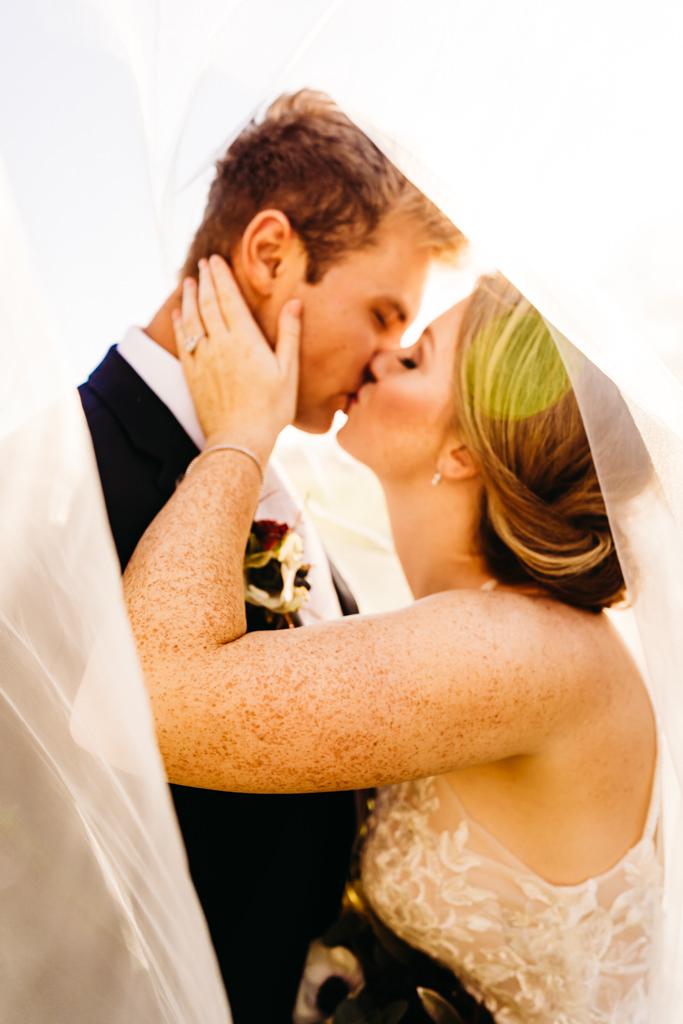 Couple kiss under the bride's veil as part of their Minneapolis wedding photography album