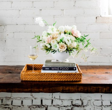 Bouquet with books and glass of white white in a wicker tray on a ledge, photographed for Minnesota Brand Photographer