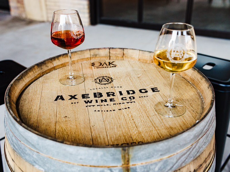 Minnesota Urban Winery Branding photos of two wine glasses on a barrel that has the words Axebridge Wine Co. on it.