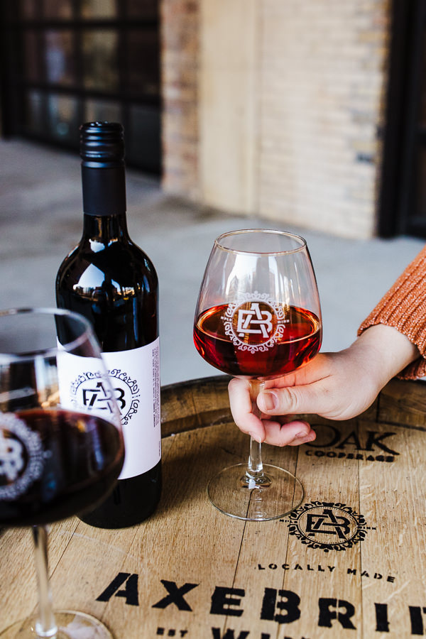 Photo of a hand holding a wine glasse on a table during Minneapolis Urban Winery Branding session