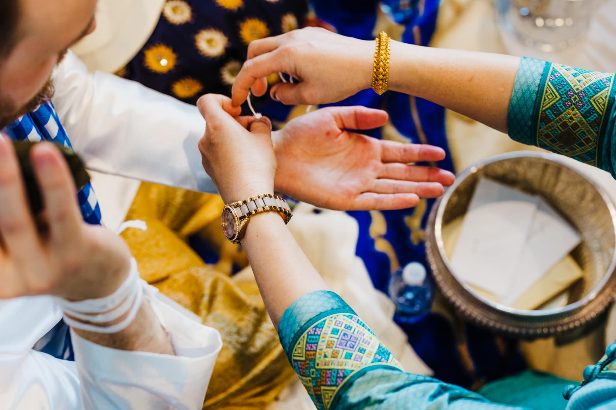 Relative ties string on groom's wrist during traditional lao wedding ceremony to bless his marriage