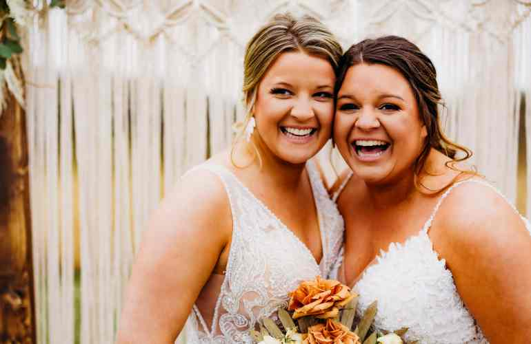 Brides stand cheek to cheek and laugh together, showing us how to look better in photos