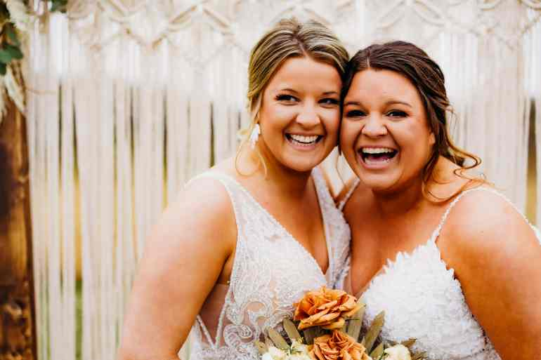 Brides stand cheek to cheek and