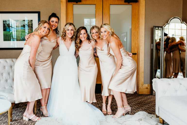 Minneapolis Wedding Photographer captures brides and bridesmaids smiling at the camera after the bridesmaid reveal