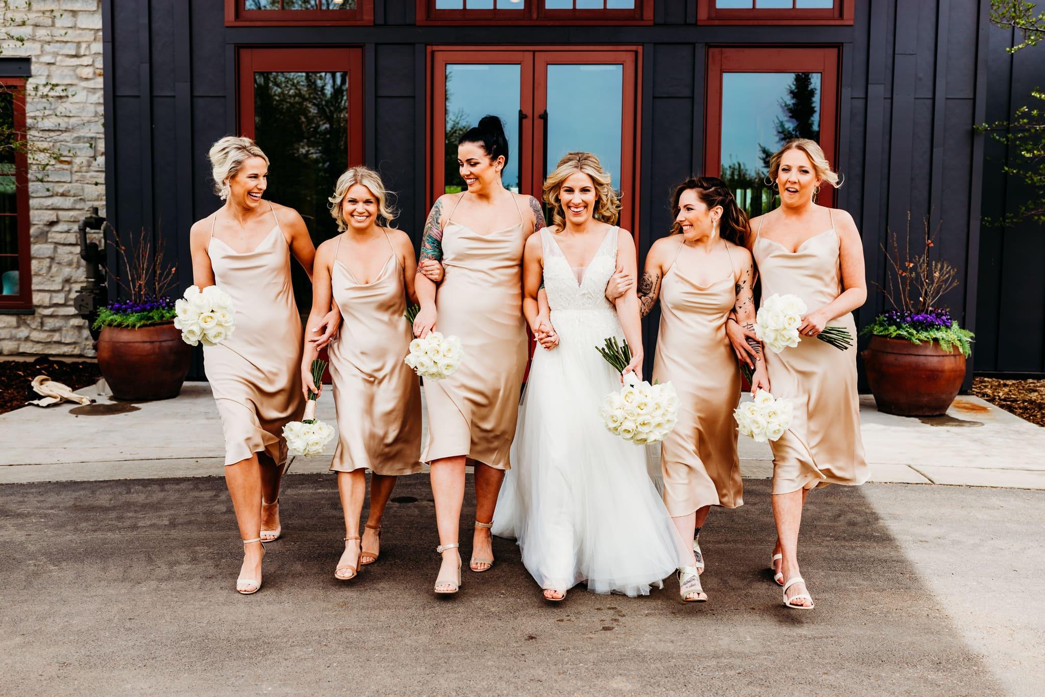 Bride walks outside at her Hazeltine National Golf Club wedding with her bridesmaids