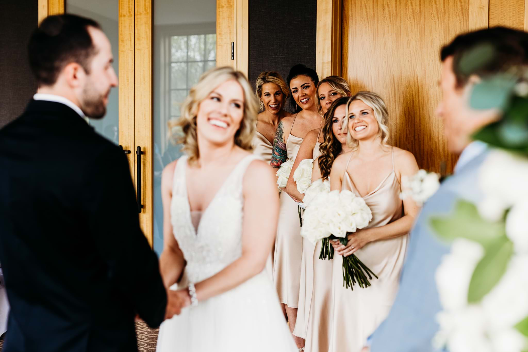 bridesmaid smile and watch as bride and groom hold hands during ceremony at their Hazeltine national golf course wedding
