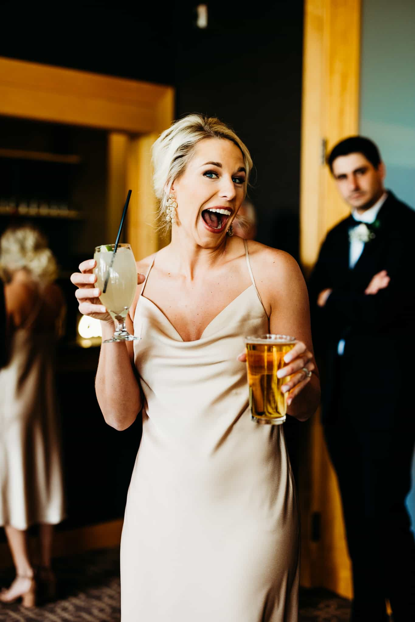 Bridesmaid smiles with a beer in one hand and margarita in the other as she celebrates her new sister-in-laws Hazeltine National Golf club wedding