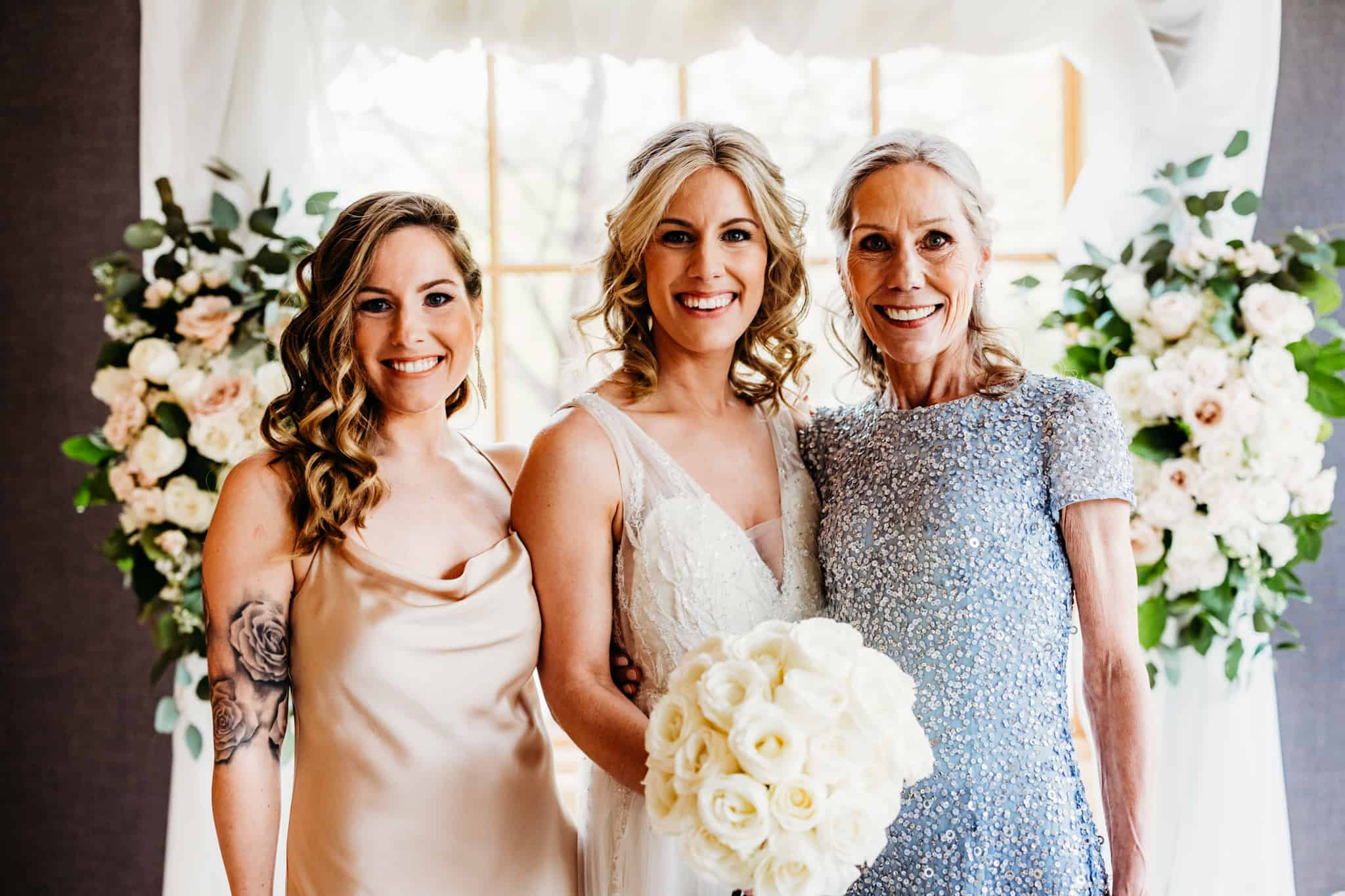 Bride, her mom and sister smile together at the camera at a hazeltine national golf club wedding
