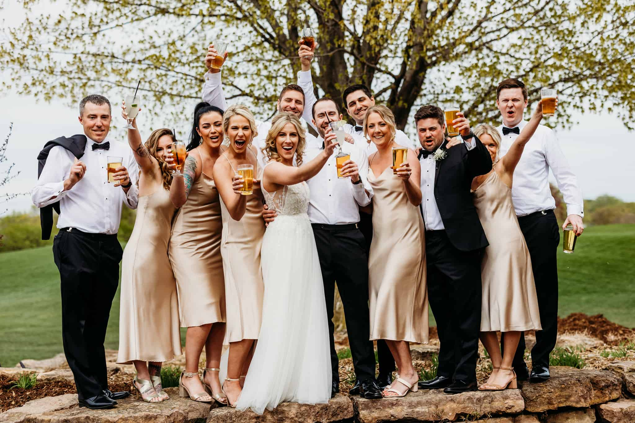 Couple and their wedding party celebrate with a drink all huddled together outside of their Hazeltine National Golf Club wedding