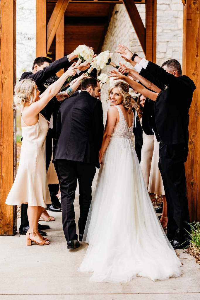 Minneapolis Wedding Photographer captures couple walking through tunnel of their wedding party, bride smiles over her shoulder