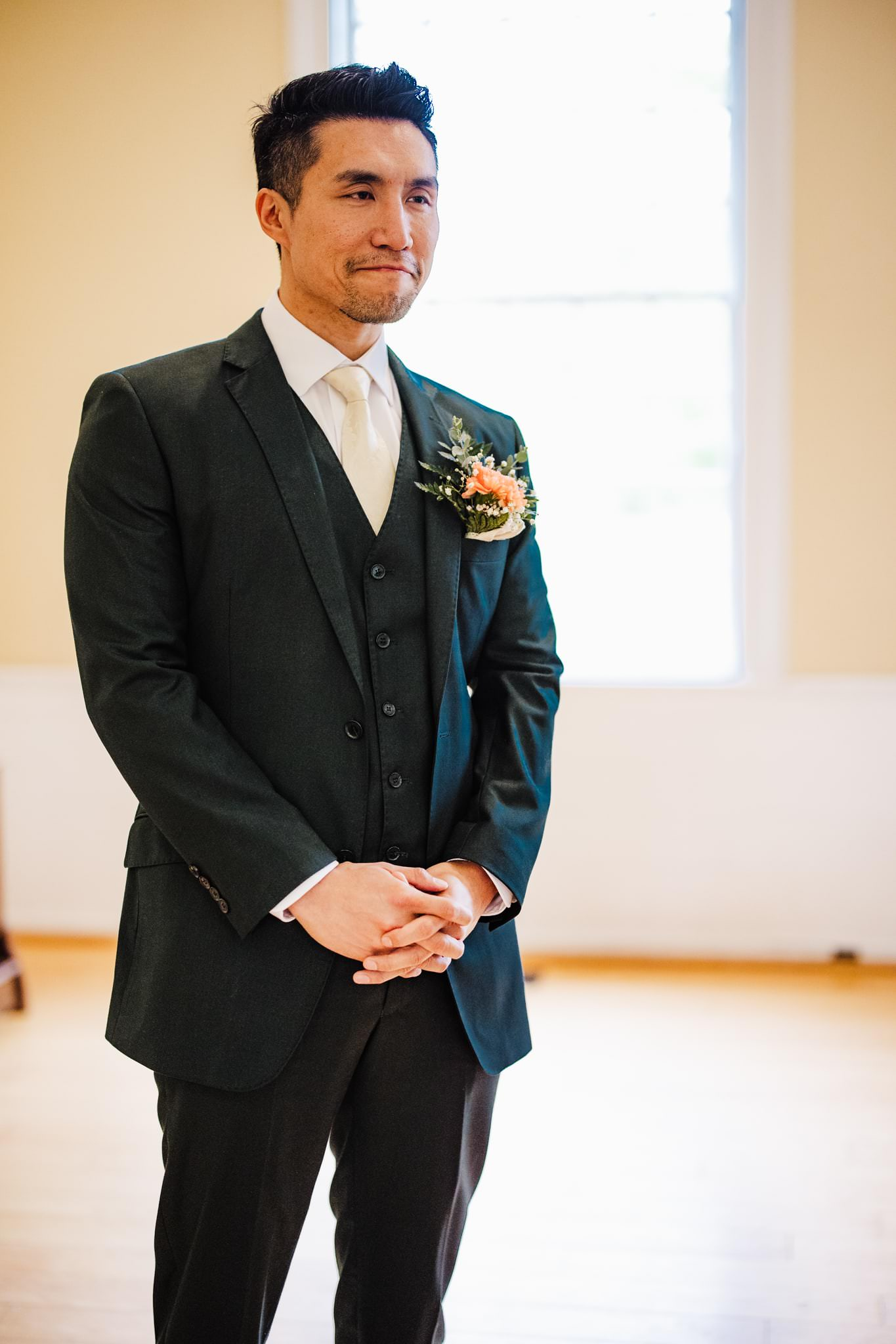 Groom watches as his bride makes her way down the aisle at their mill race village wedding
