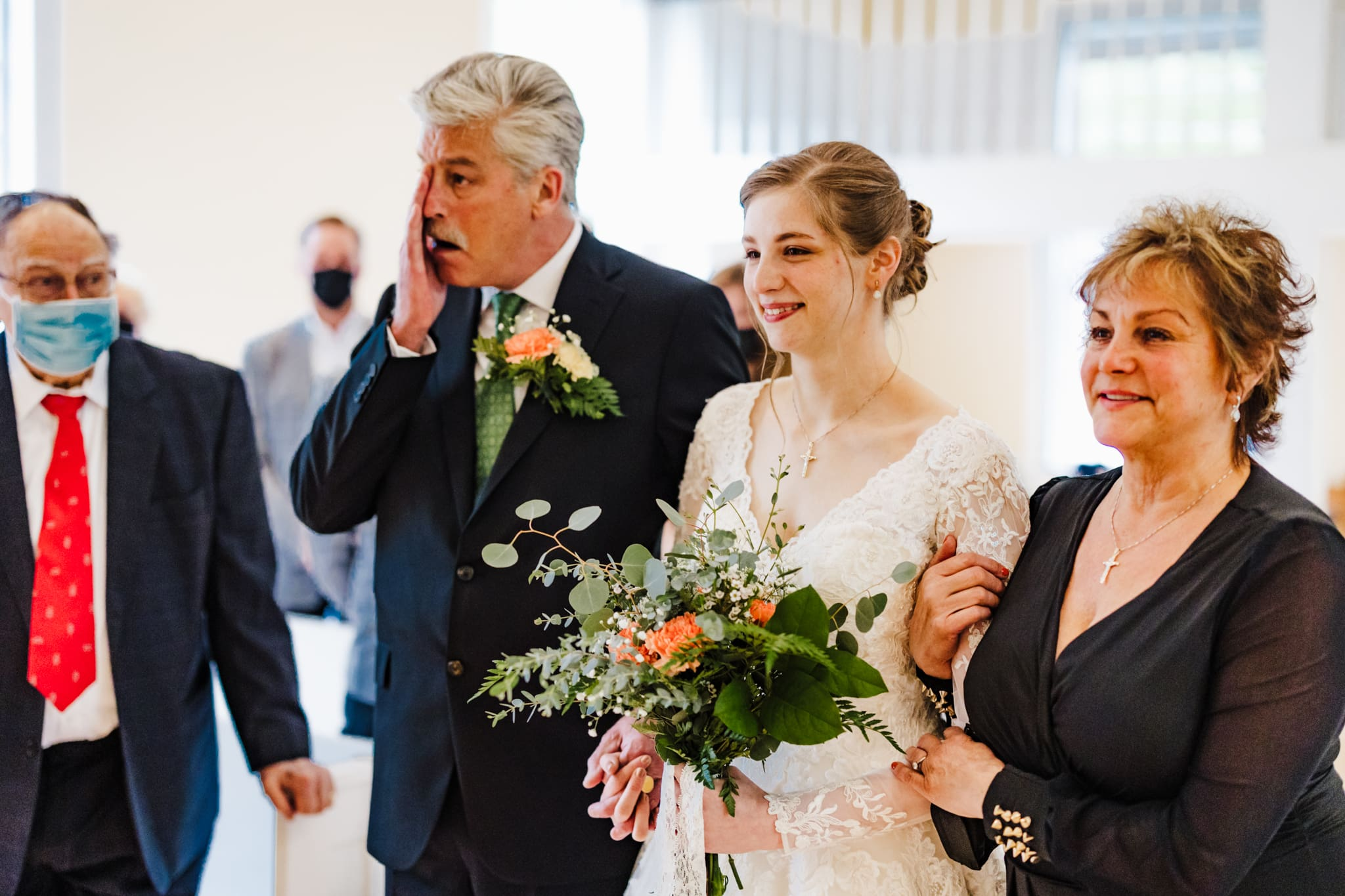 Mom and dad stand with their daughter as she comes down the aisle at her Mill Race Village wedding