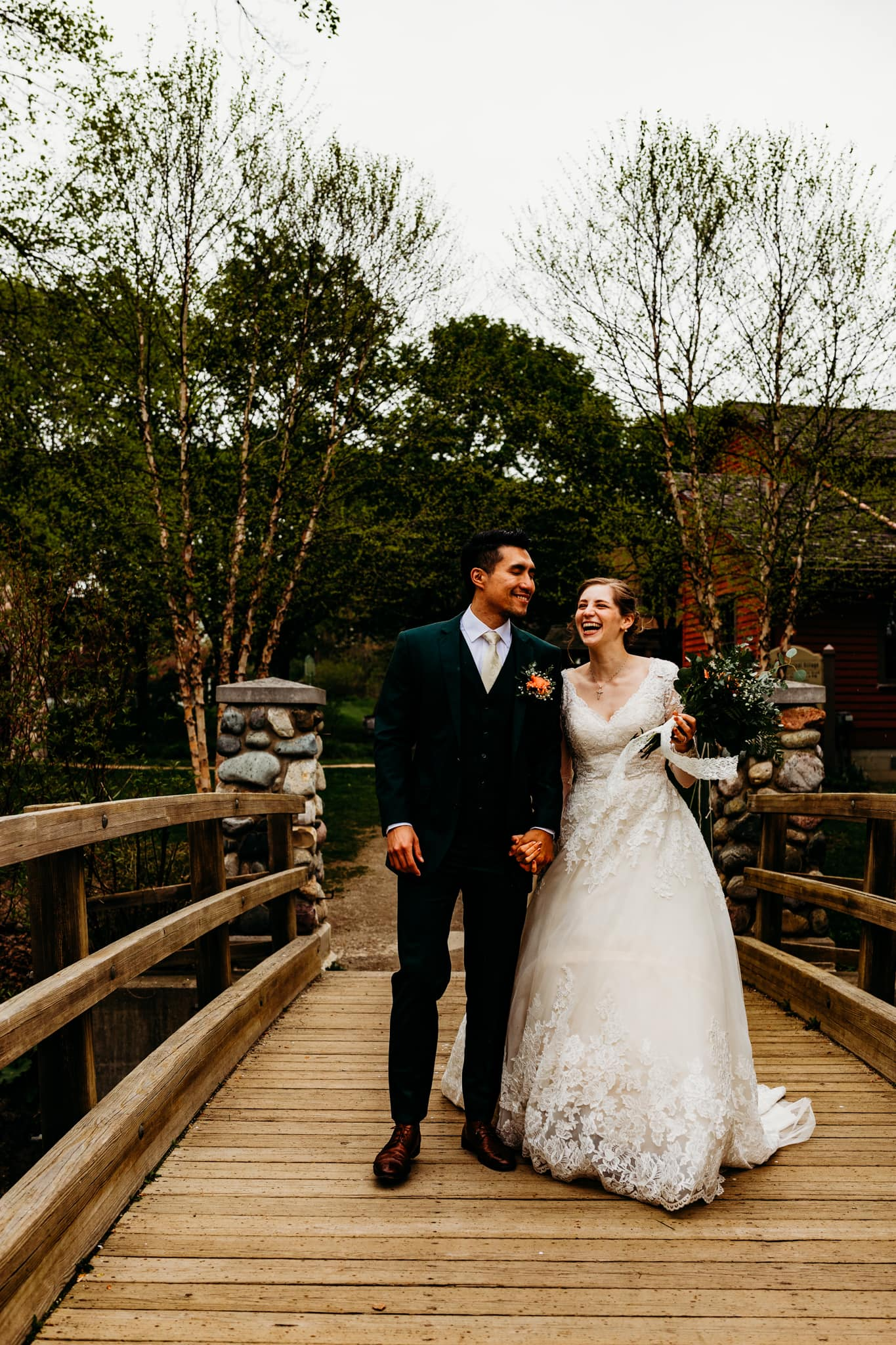 Newlyweds laugh on the bridge together that led to their Mill Race Village wedding