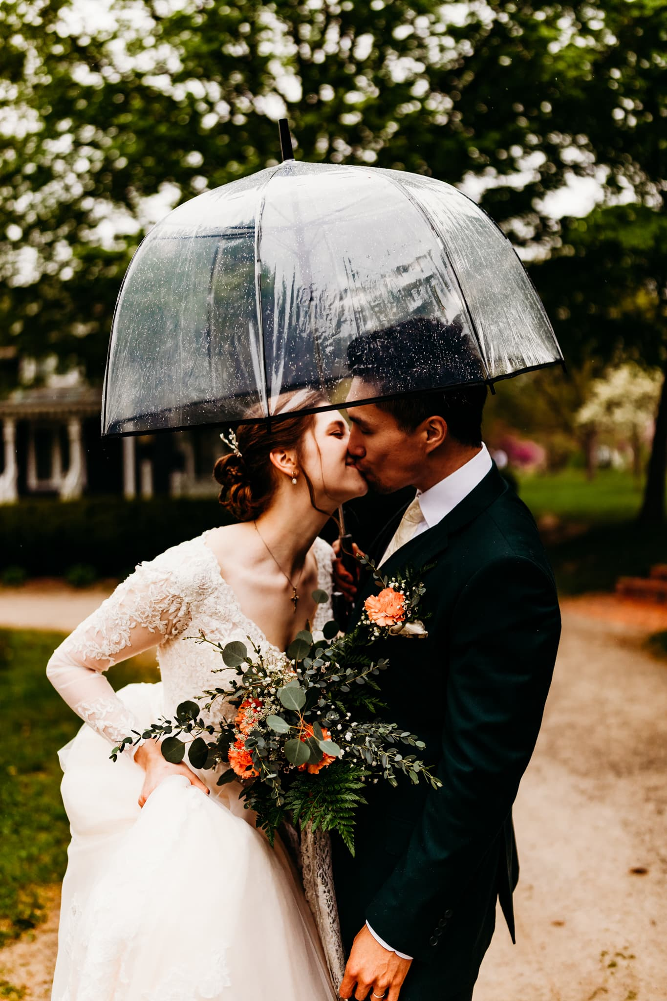Couple kisses under an umbrella at their Mill Race Village wedding