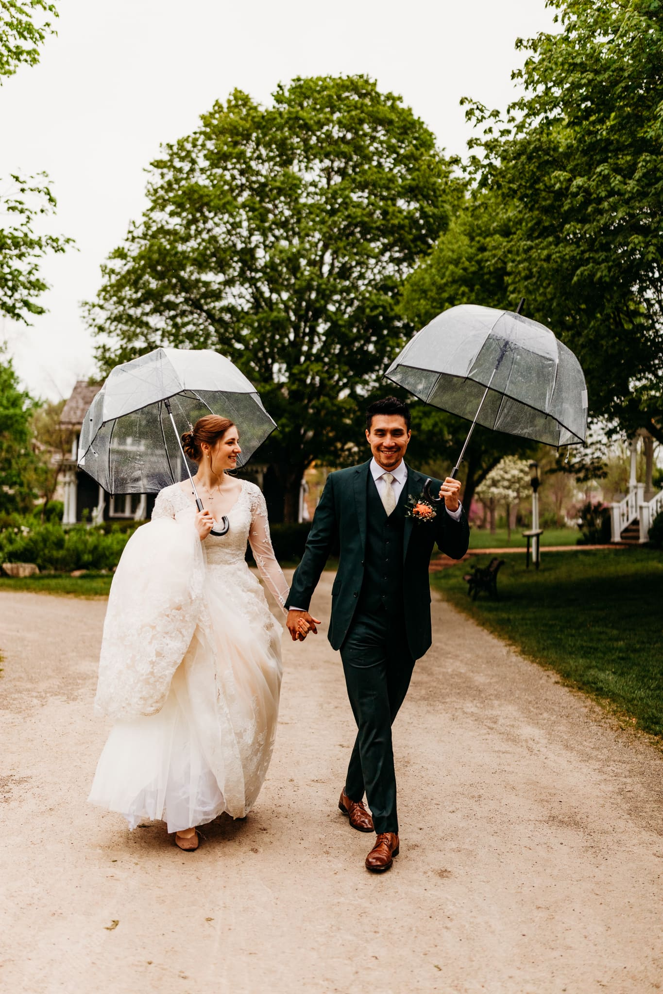 Couple walks together under umbrellas in the rain after their wedding at Mill Race Village