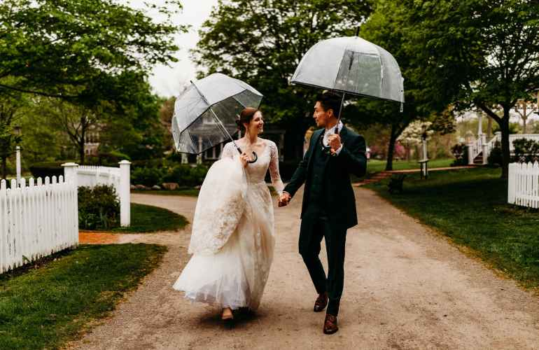 Couple strolls down the dirt road in Mill Race Village after their wedding