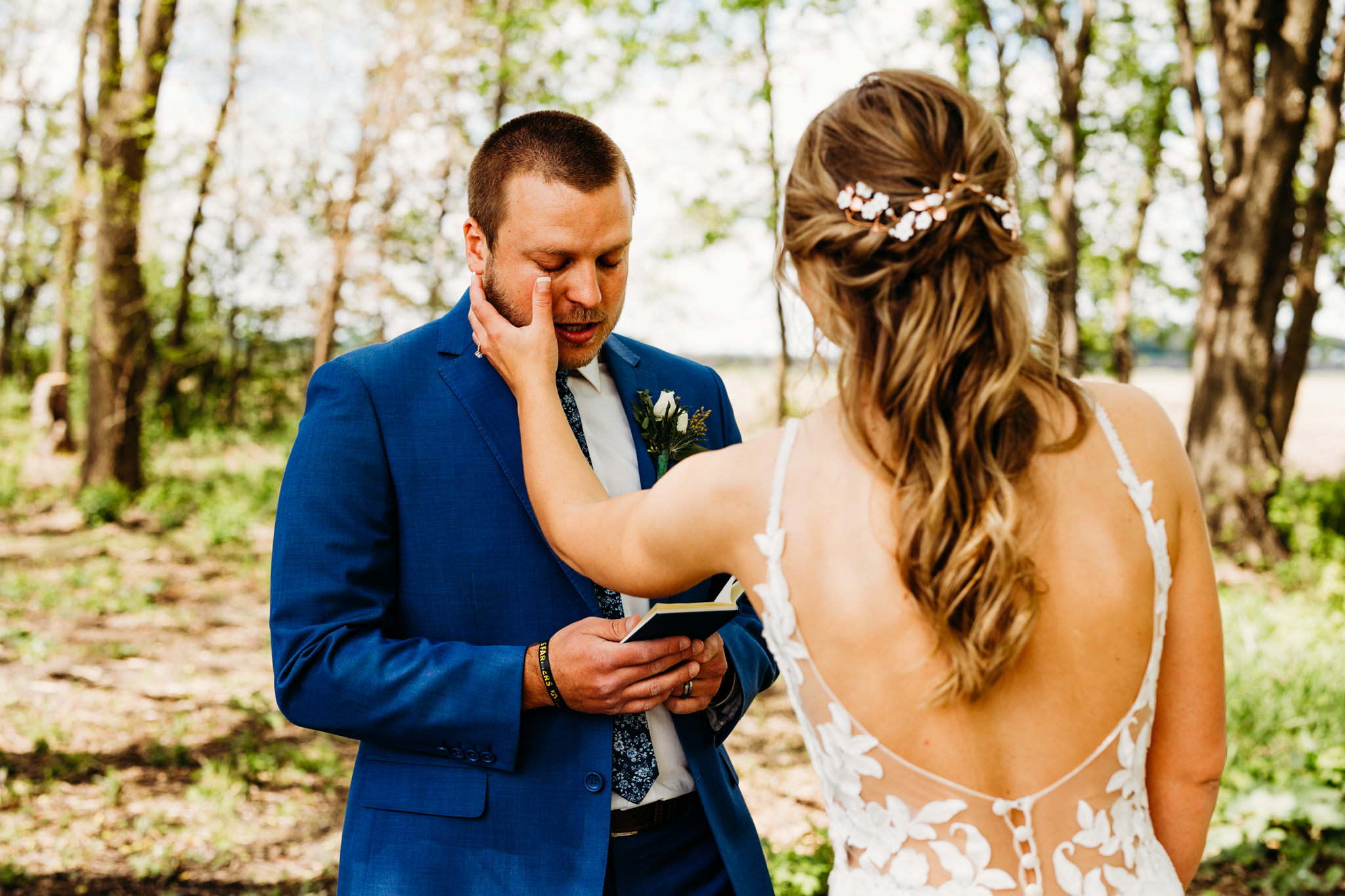 Emotional wedding photography captures bride wiping her groom's tear as he reads his vows
