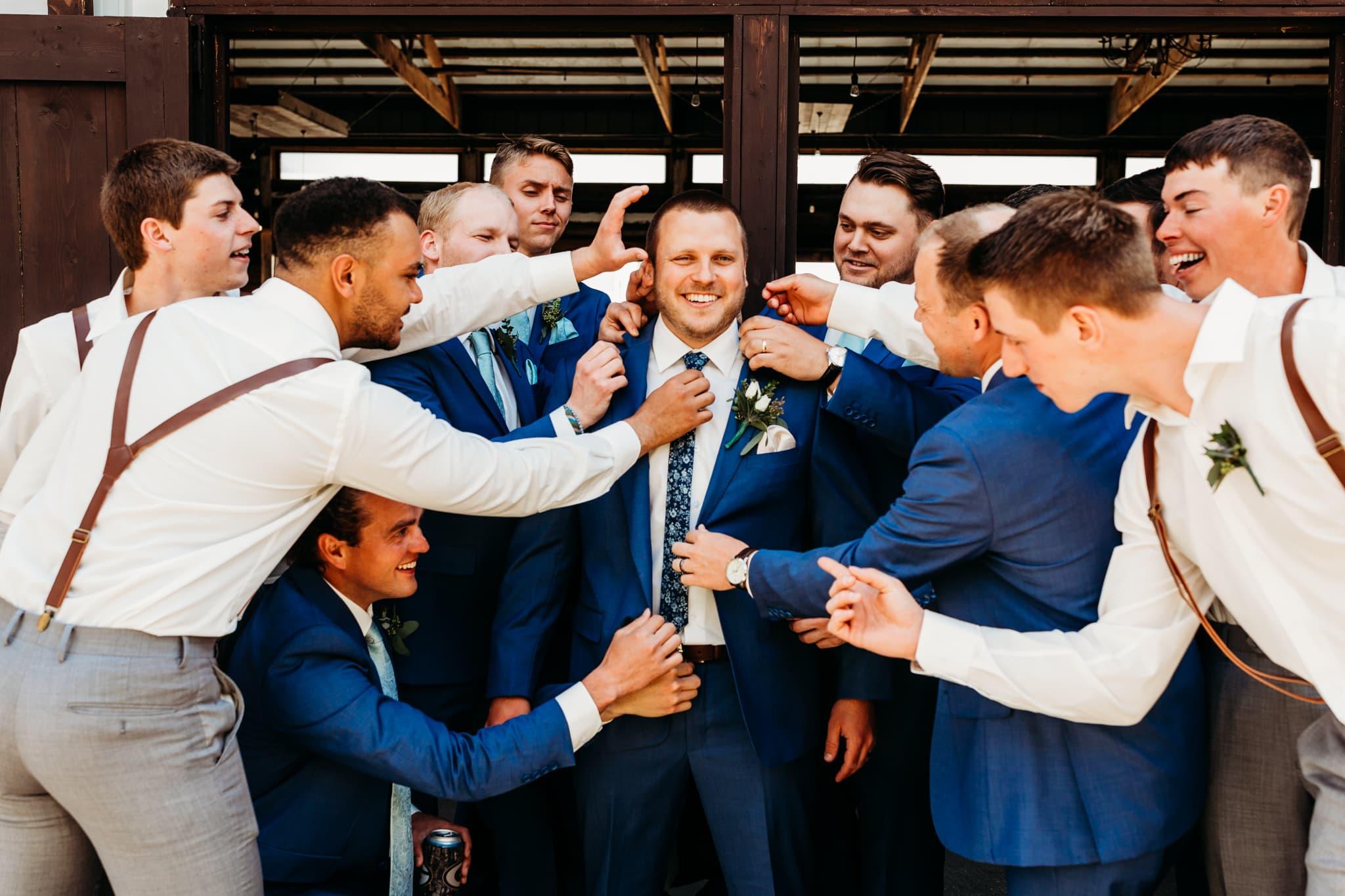 Groomsmen jokingly help the groom get ready at his schroeder farm wedding