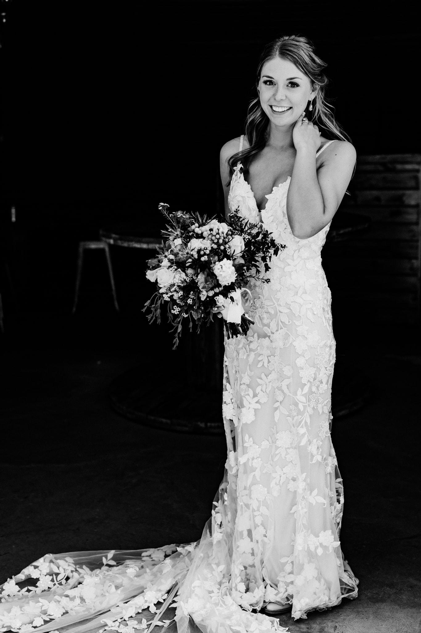 Bride smiles at the camera wit her bouquet during her Schroeder Farm Wedding