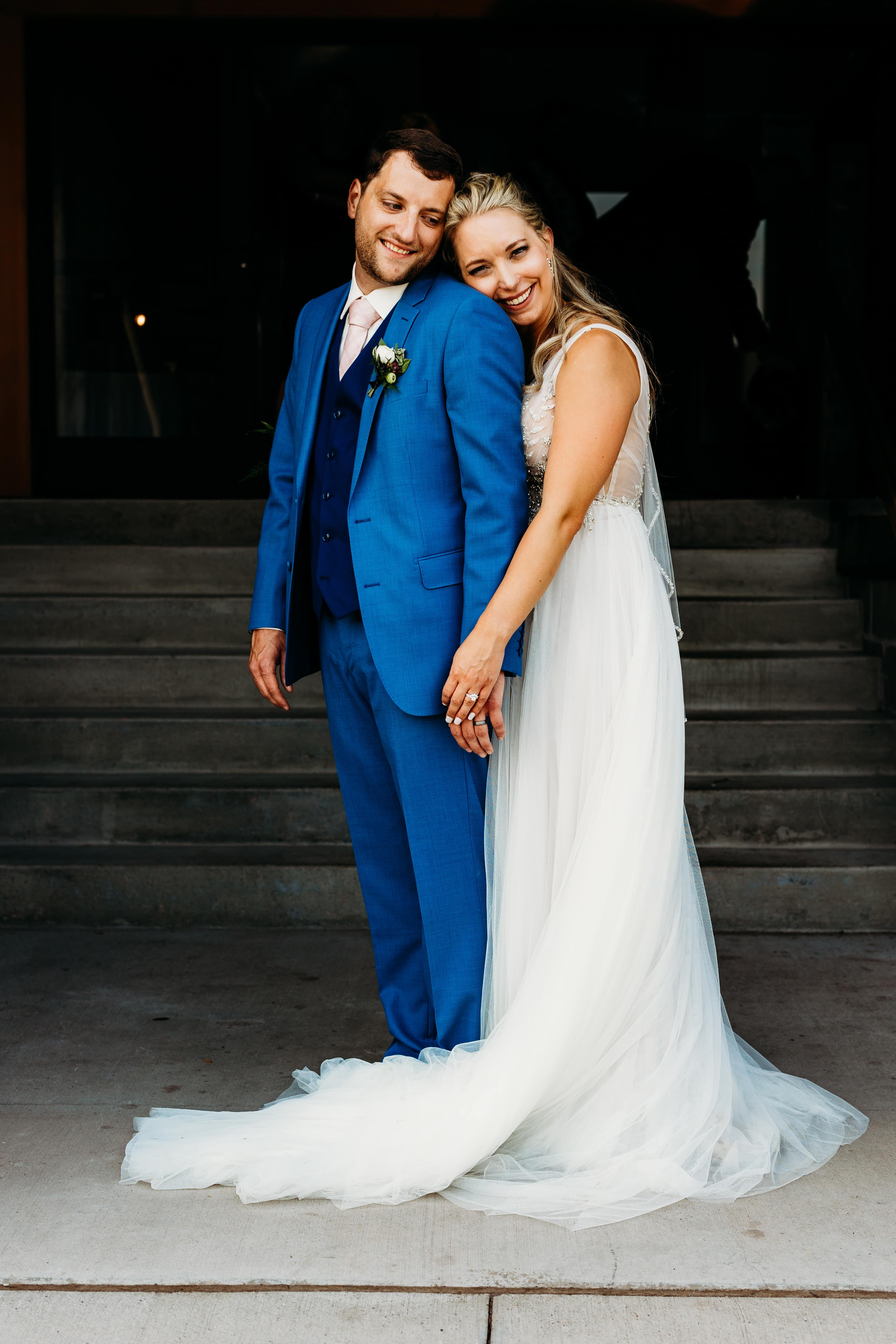 Bride and groom lean on one another and bride smiles at the camera outside her Duluth Malting Building wedding