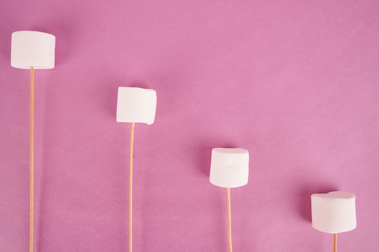 Fluffy marshmallows with sticks on purple background