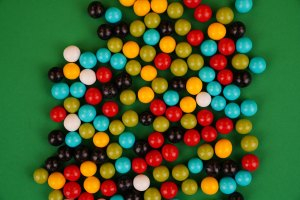 Multicolored round dragee candies on green background
