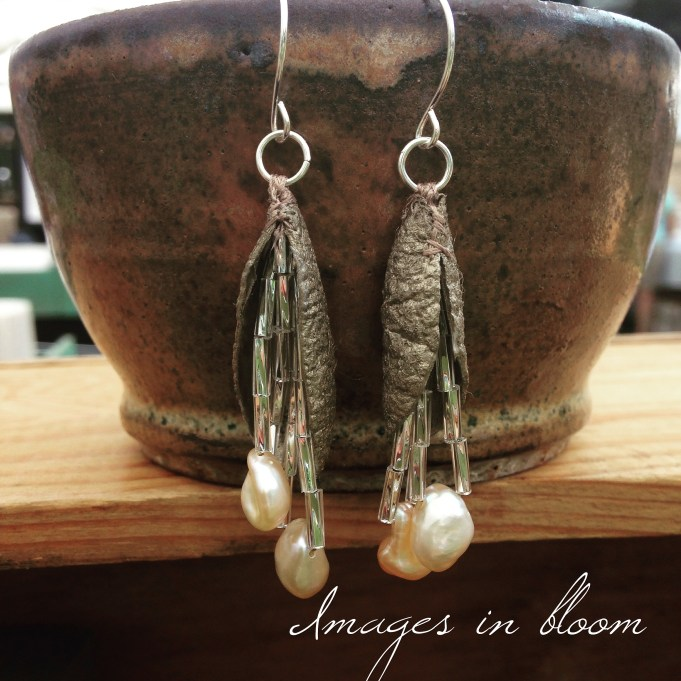 Quarter of cocoons, painted platinum, stitched at the top to create open pod shapes, with dangles of silver bugle beads and freshwater pearls. The ear wires are sterling.