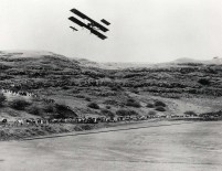 As the biplane with its gigantic winds swept over the grass field and rose into the air there was a general whoop of exultation and spontaneous applause from spectators.