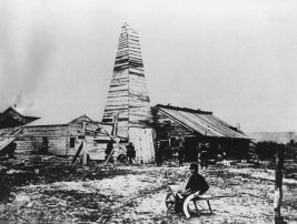 """This is the well near Titusville, Pennsylvania which pumped the petroleum industry into existence 100 years ago. The picture was taken four years after Col. Edwin L. Drake struck oil on August 27, 1859 near Titusville, Pennsylvania. Seated in the foreground is """"Uncle"""" Billy Smith, Drake's drilling foreman, who was first to notice a dark green liquid bubbling at the top of the hole. His cry of """"Oil, struck oil."""" Signaled success of the world's first oil well and set off the world's first oil book. The Drake well with a depth of 9½ feet, pumped 3 barrels a day. (AP Photo)"""