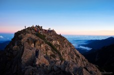 A crowd of hikers gathers on Jade Mountain Main Peak to view the sunrise.