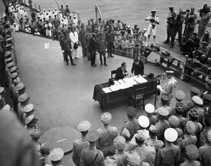 Original caption: Tokyo, Japan: Ceremonies of the Japanese surrender on board the battleship Missouri, 1945. Japanese Foreign Minister Shigemitsu signs as MacArthur braodcasts ceremonies. September 2, 1945 Tokyo, Japan