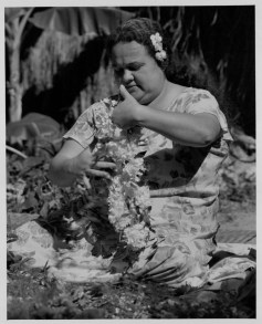 Julia Niu entwining a carnation lei with maile-PP-33-10-007-1935