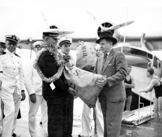 Pan American Clipper executive officer R. O. H. Sullivan hands over the first sacks of air mail delivered to Hawaii-PP-1-7-005-1935