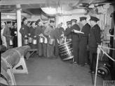 RUM RATION ABOARD HMS KING GEORGE V, 1940 (A 1777) Below deck, a line of seamen queue to collect the daily rum ration for their mess. Each man is holding a jug or bucket. The rum is being issued from a large barrel with 'THE KING - GOD BLESS HIM' on it. Royal Marines issue the rum with measuring jugs while a Royal Navy Petty Officer and Sub-Lieutenant observe. Copyright: © IWM. Original Source: http://www.iwm.org.uk/collections/item/object/205185139