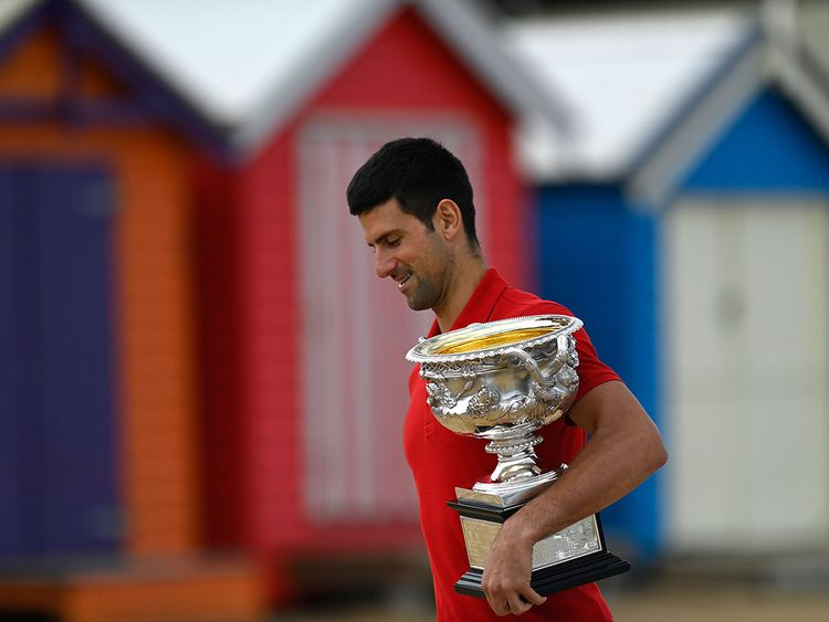 Novak Djokovic with the Australian Open trophy at Brighton Beach in Melbourne