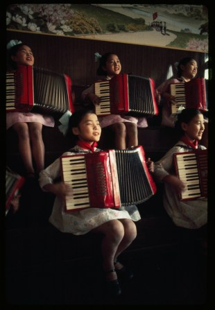 North Korean school girls practice playing accordions, August 1974.