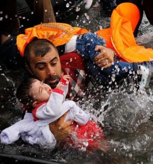 Un padre desembarca con su hijo en Lesbos.