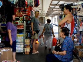 Fig.11: My grandmother and father chatting with various shop owners at the market