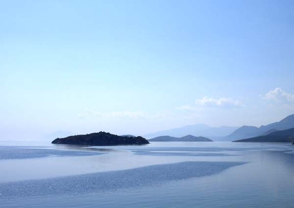 minimalist photo with blue water and sky and a dark island
