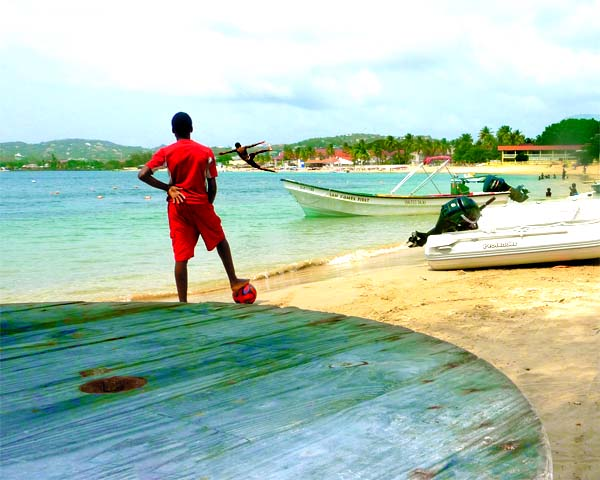 Soccer player at beach with boats and table