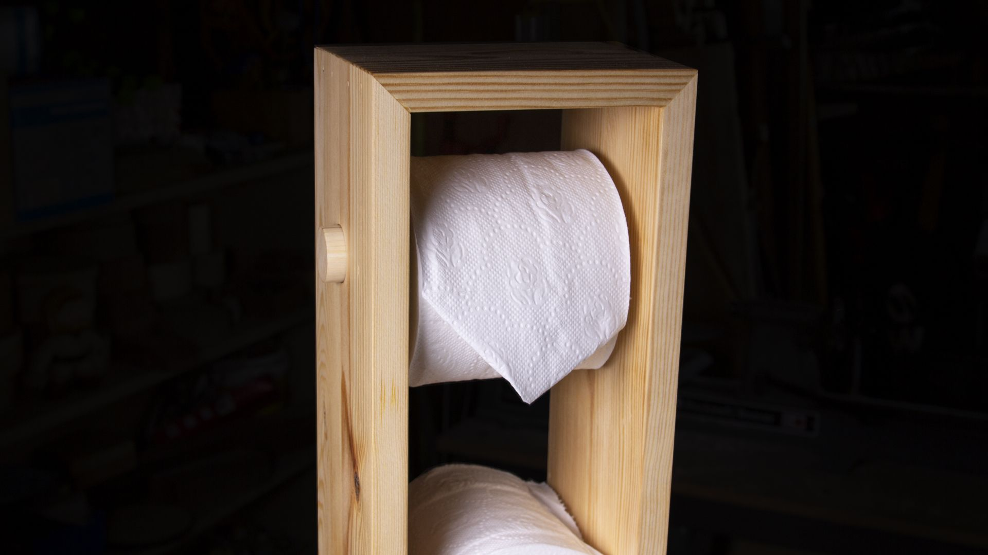 A toilet paper tower made out of scrap pine wood.