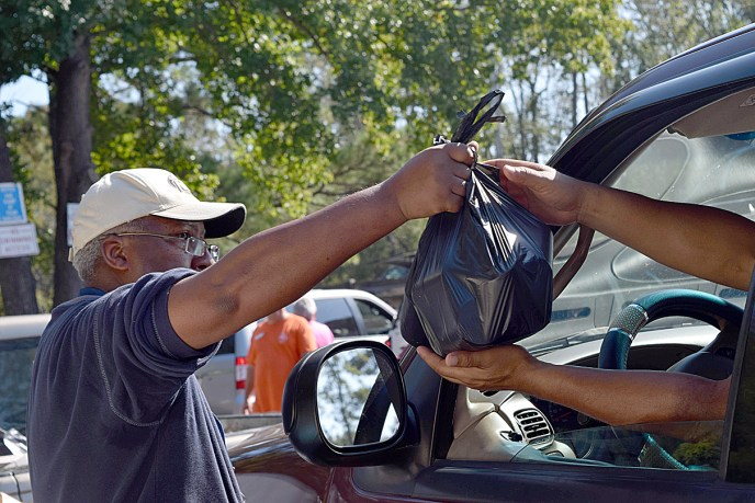 A man hands a black plastic bag to an individual in a vehicle