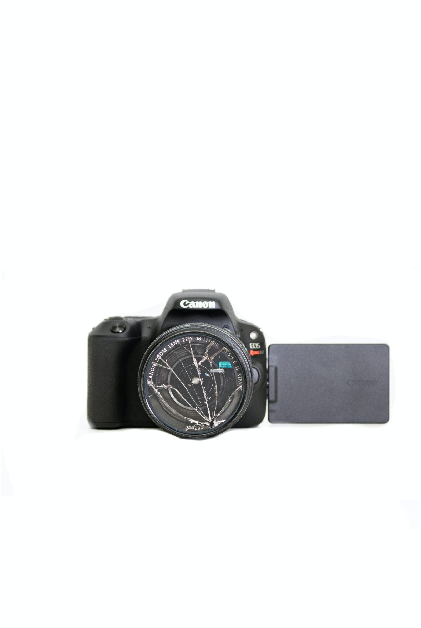 A DSLR camera with a broken lens is in front of a white background.