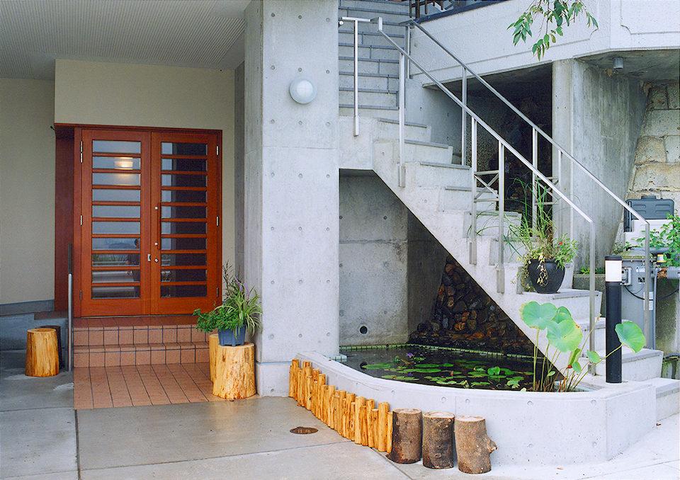 ホームエレベーター付きバリアフリー鉄筋コンクリート造打ち放し3階建て注文住宅の新築設計・デザイン コンクリート階段と玄関
