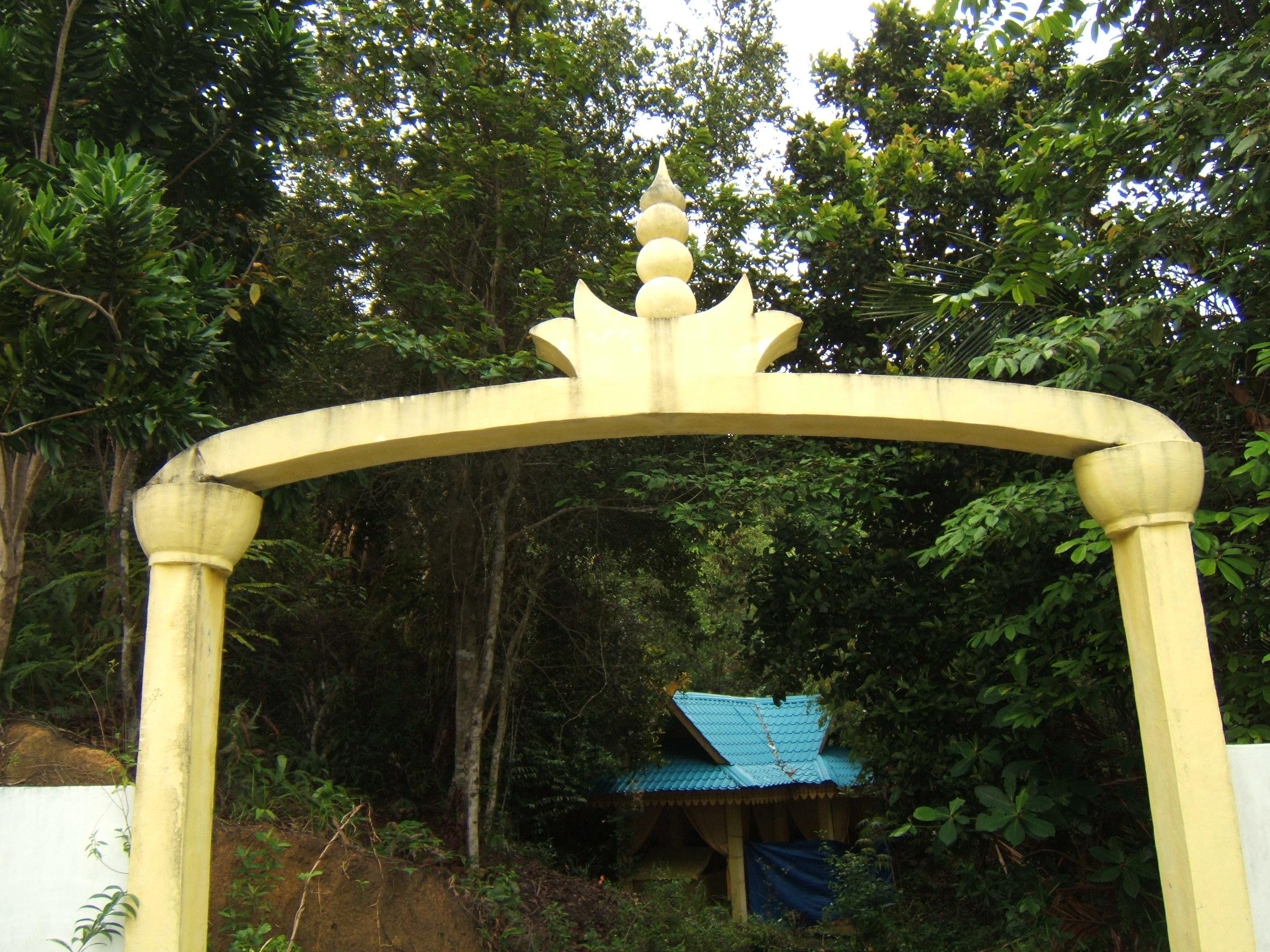 gapura, pintu masuk ke perigi, perigi tertutup dengan selayar warna kuning, ada bangunan beratap tilux warna biru sumbangan dari orang Singapura, entah apa maksudnya perigi itu diselayari warna kuning.