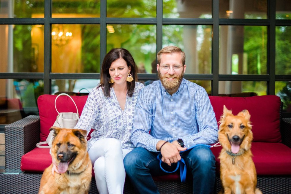 When You Know, You Know: Celebrating 10 Years Together - I'm Fixin' To - @imfixintoblog |10 Year Anniversary by popular NC lifestyle blog, I'm Fixin' To: image of a husband and wife sitting on a outdoor wicker couch with red cushions next to their two dogs.
