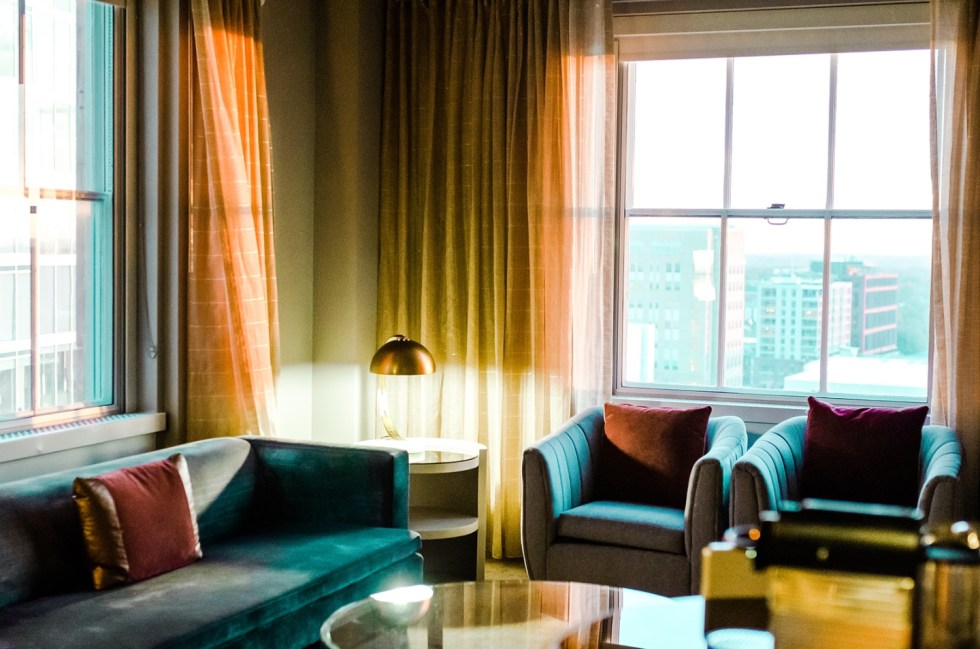 23 Awesome Things To Do in Durham - I'm Fixin' To - @imfixintoblog | Things to do in Durham by popular NC travel blog, I'm Fixin' To: image of a sitting area at the 21c Museum hotel with with blue velvet furniture, mid century modern lamps, and a round glass coffee table.
