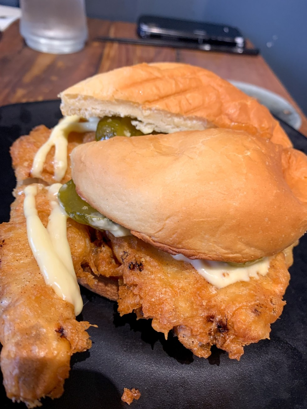 23 Awesome Things To Do in Durham - I'm Fixin' To - @imfixintoblog | Things to do in Durham by popular NC travel blog, I'm Fixin' To: image of a fried fish sandwich on black plate.